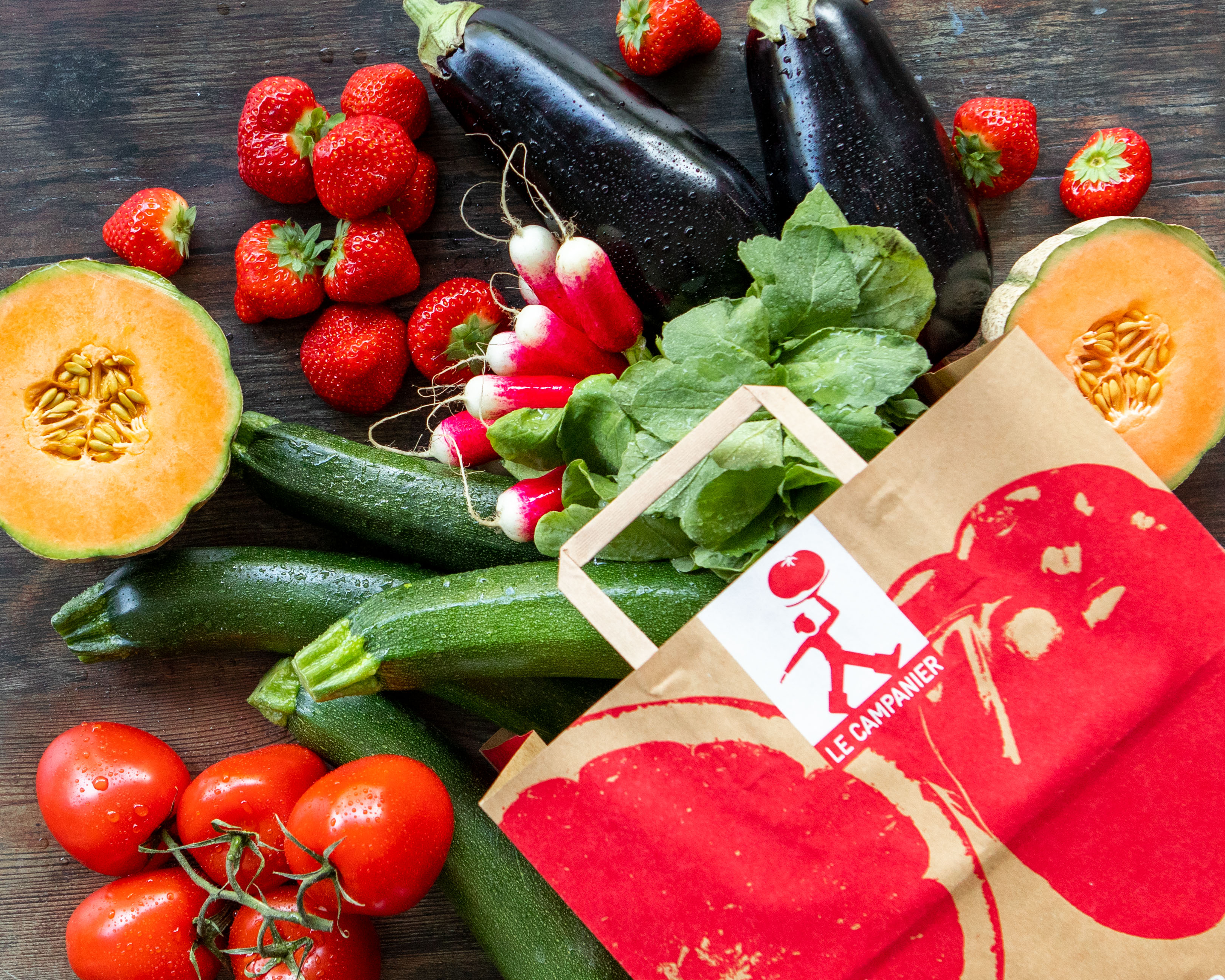 panier de fruits et légumes bio : radis, fraises,aubergines, courgettes, tomates, melon